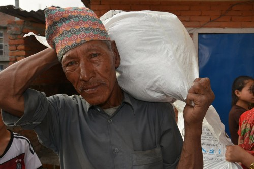 An elderly man heads home with food for his family